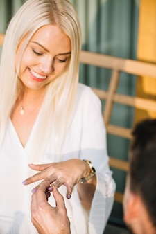Smiling blonde young woman looking at her ring given by his boyfriend