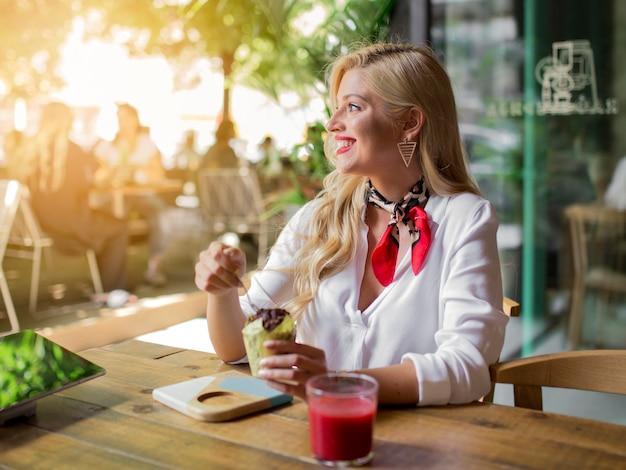 Улыбающаяся молодая блондинка сидит в кафе и ест булочки