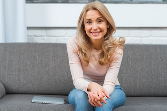 Smiling blonde young woman sitting on gray sofa with laptop