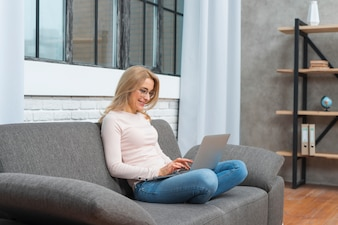 Smiling blonde young woman sitting on sofa typing on laptop at home