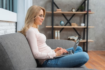 Smiling blonde young woman sitting on sofa typing over laptop