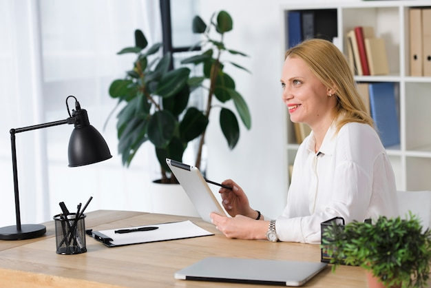 Smiling blonde young woman sitting at workplace using digital tablet