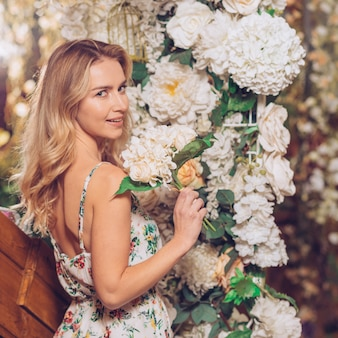 Smiling blonde young woman standing in front of flower decoration holding flower bouquet