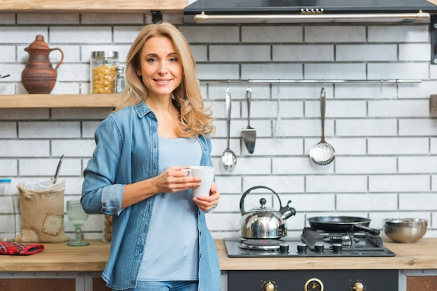 Smiling blonde young woman standing near the gas stove holding white coffee cup