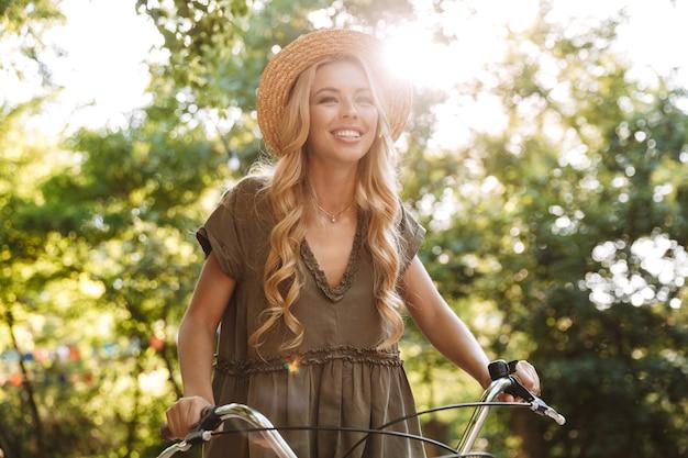 밀짚 모자에 웃는 blondy 여자 자전거를 타고 야외에서 멀리보고