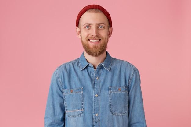 赤い厚いあごひげを生やした赤い帽子をかぶった青い目の男は、白い健康な歯を見せて幸せ喜びの喜びを感じ、ファッショナブルなデニムシャツを着て、孤立している