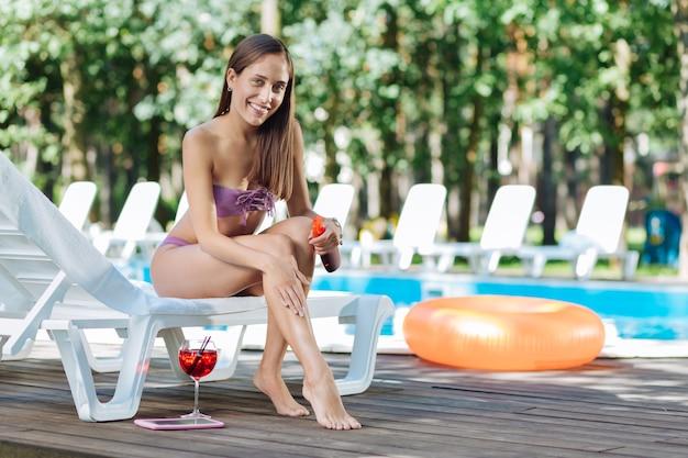 Улыбающаяся голубоглазая женщина в модном купальном костюме с защитой от солнца перед тем, как лечь под солнце