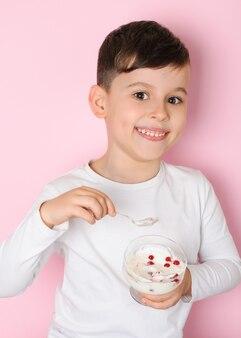 ピンクの表面に健康的なデザートベリーヨーグルトを食べる白いtシャツで6歳の笑顔の男の子