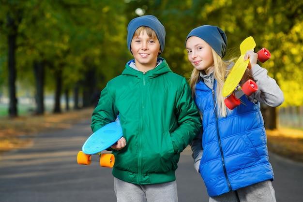 Улыбающийся мальчик и девочка, держа пенни доски