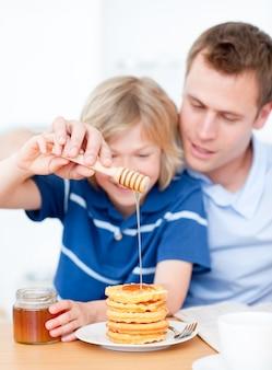 笑顔の少年と父親がワッフルに蜂蜜を置く