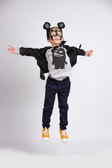 Smiling boy in black bat costume jumping over gray wall with lots of space.