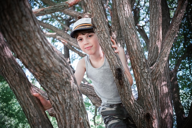 Smiling boy in cap and undershirt climbing tree branches.