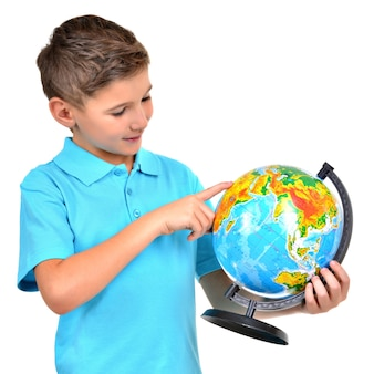 Smiling boy in casual holding globe with in hands and points on it isolated on white