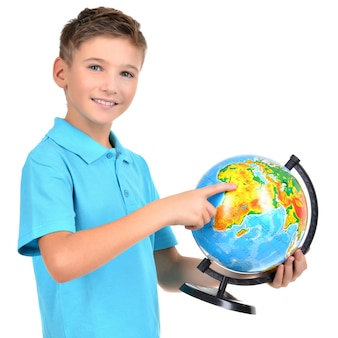 Smiling boy in casual  holding globe with in hands and points on it -  isolated on white