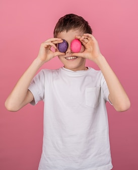 Smiling boy covering eyes with colorful eggs isolated on pink wall
