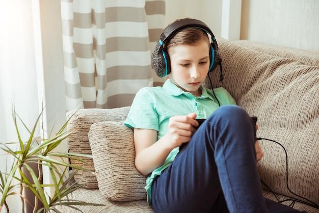 웃는 소년은 헤드폰과 태블릿으로 숙제를합니다. 격리에서 원격 학습