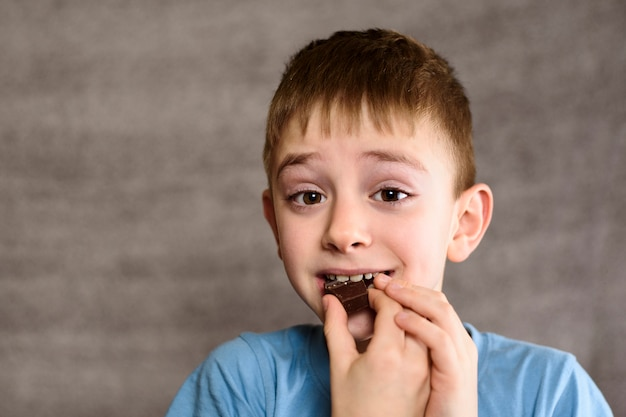 Smiling boy eating a piece of chocolate
