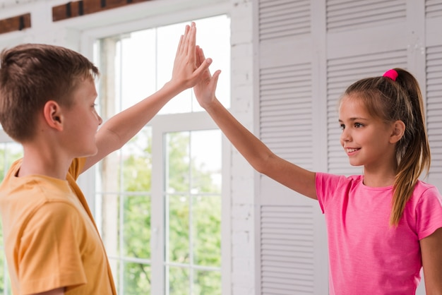 Smiling boy and girl giving high five near the window