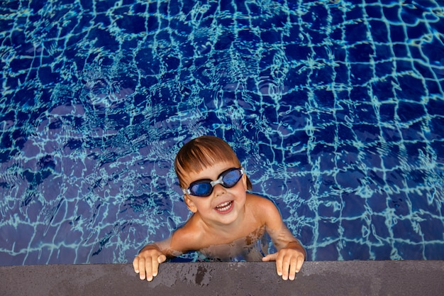 Smiling boy in goggles in water near edge of pool