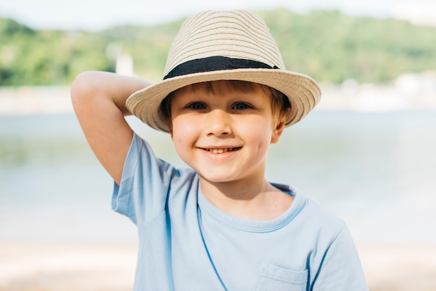 Smiling boy in hat enjoying sunlight