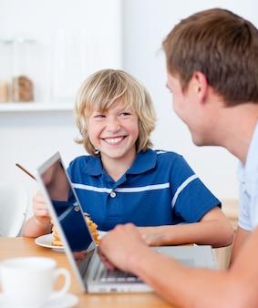 ラップトップを使って父親が朝食をしている笑顔の少年