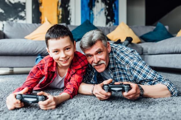 Ragazzo sorridente e suo nonno che giocano insieme ai videogiochi a casa, sdraiato sul pavimento.