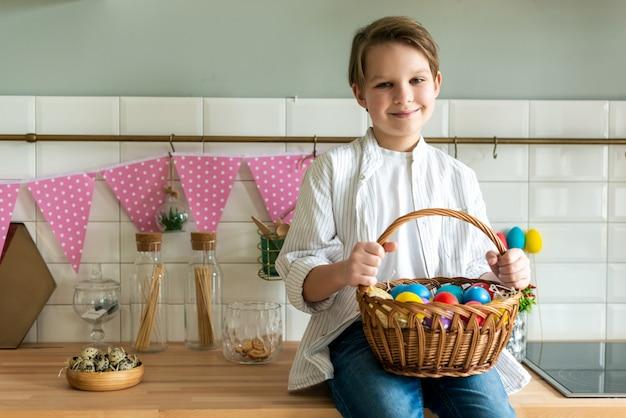 부활절 달걀 바구니를 들고 웃는 소년.