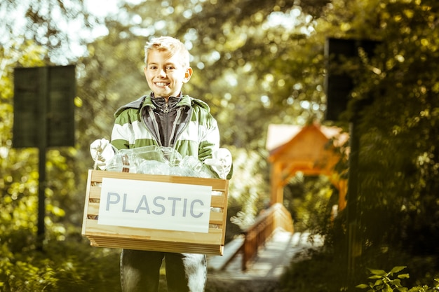 A smiling boy holding a box of plastic trash in forest on a fine day
