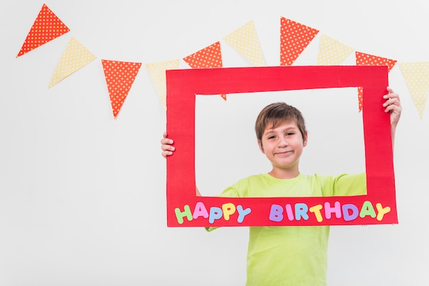 Smiling boy holding frame with happy birthday frame against wall decorated with bunting