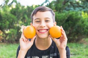 Smiling boy holding fresh whole oranges near his cheeks