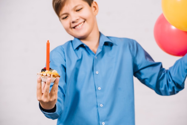 Smiling boy holding muffin with red candle and balloon against white backdrop