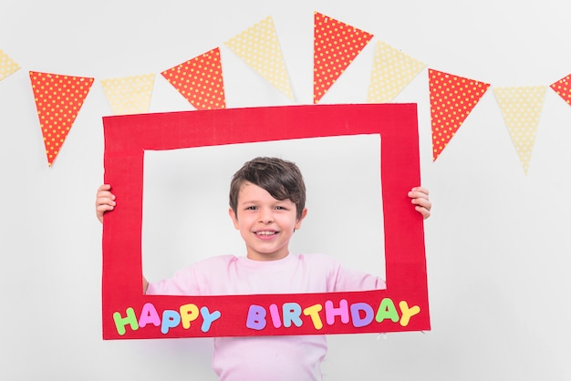 Smiling boy holding red birthday frame in party