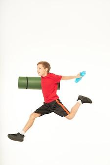 공중에서 점프하는 동안 롤 운동 매트와 상쾌한 스포츠 음료를 들고 웃는 소년. 흰색 배경에 고립