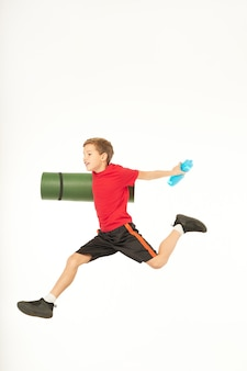 Smiling boy holding rolled exercise mat and refreshing sports drink while jumping in the air. isolated on white background
