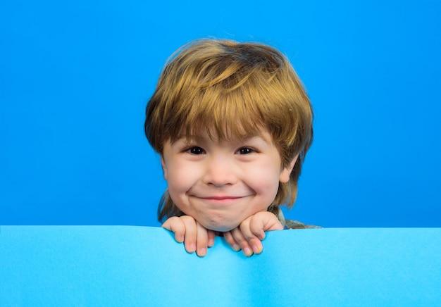 Улыбающийся мальчик держит пустую доску ребенок мальчик держит пустой рекламный щит маленький мальчик держит пустую рекламу
