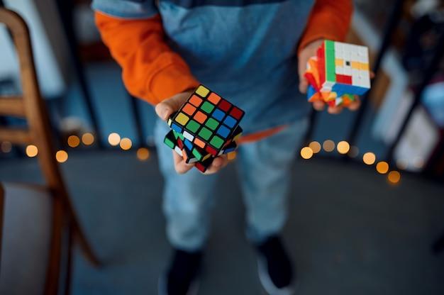 Улыбающийся мальчик держит в руках кубик-головоломку. игрушка для тренировки мозга и логического мышления, творческой игры, решения сложных задач.