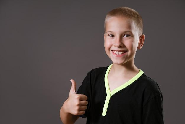 Улыбающийся мальчик в черной футболке с серой стеной, подняв палец вверх