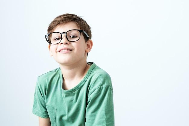 녹색 티셔츠와 안경에 웃는 소년