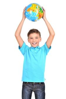 Улыбающийся мальчик в непринужденной обстановке, держа глобус в руках над его головой, изолированным на белом