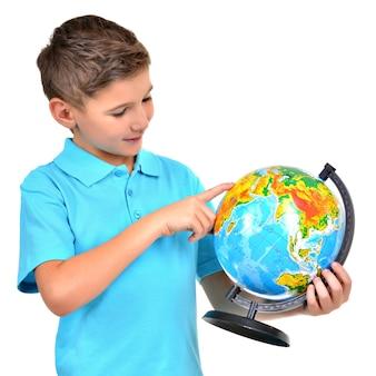 Улыбающийся мальчик в повседневной одежде держит глобус в руках и указывает на него на белом