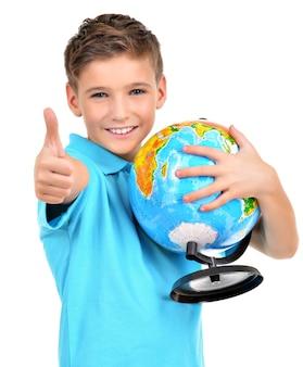 Улыбающийся мальчик в случайном холдинге глобус с большими пальцами руки вверх знак изолирован на белом