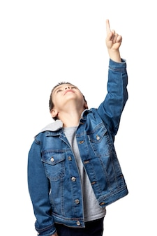 격리 된 흰색 배경에 가리키는 데님 재킷에 웃는 소년