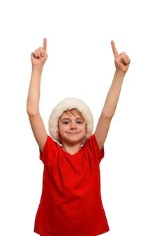Улыбающийся мальчик в шляпе санты указывает пальцами вверх. изолировать