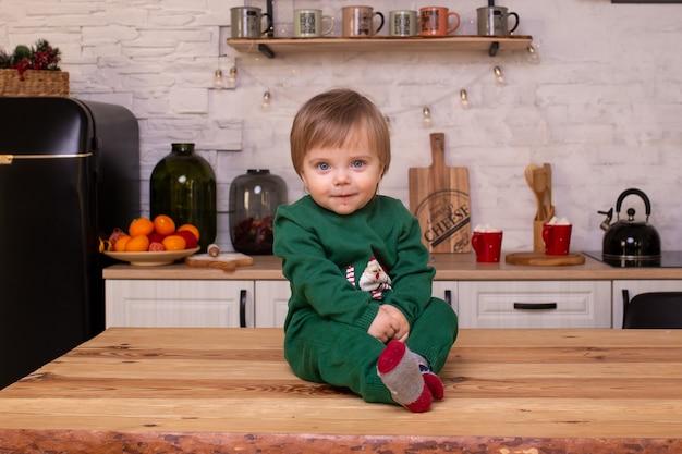 笑顔の少年は台所のテーブルに座っています