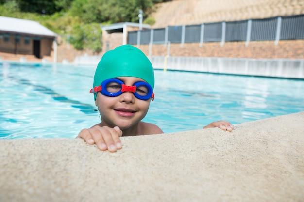 Улыбающийся мальчик, опираясь на бассейн