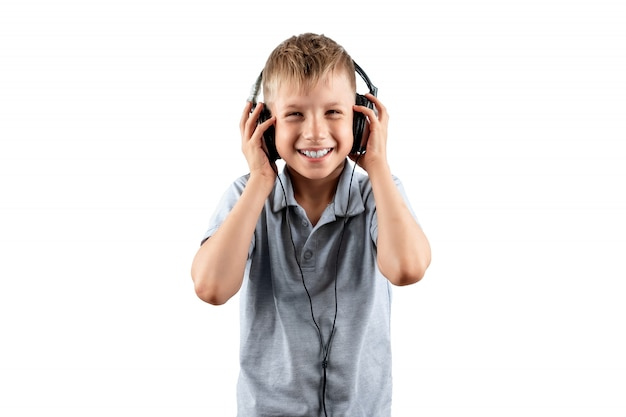 Smiling boy listens to music in big headphones isolated on a white background