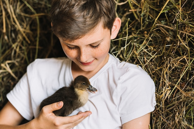 Smiling boy looking at duckling in front of hay