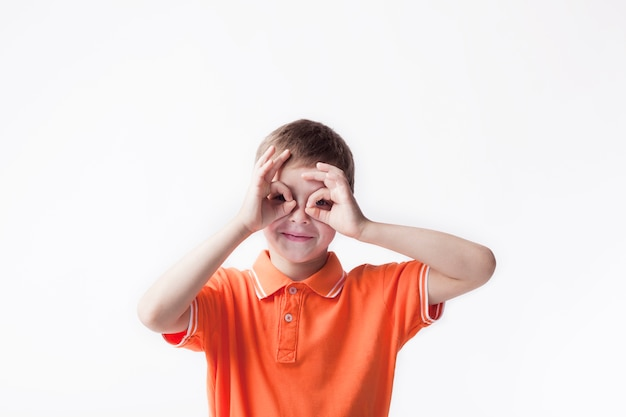 Smiling boy looking through ok hand gesture on white backdrop