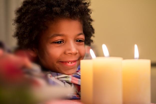 笑顔の少年はろうそくを見ます。クリスマスキャンドルの横にある幸せな子供。新年は幸せをもたらすでしょう。休日の雰囲気を感じてください。