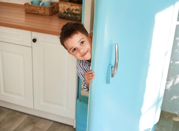笑顔の男の子が冷蔵庫のドアの後ろから外を見る